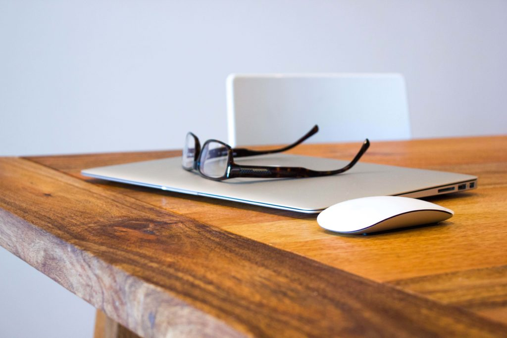 laptop on desk with glasses