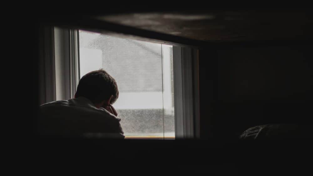man staring out the window depressed