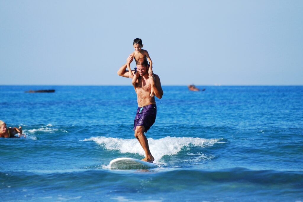 father surfing with son