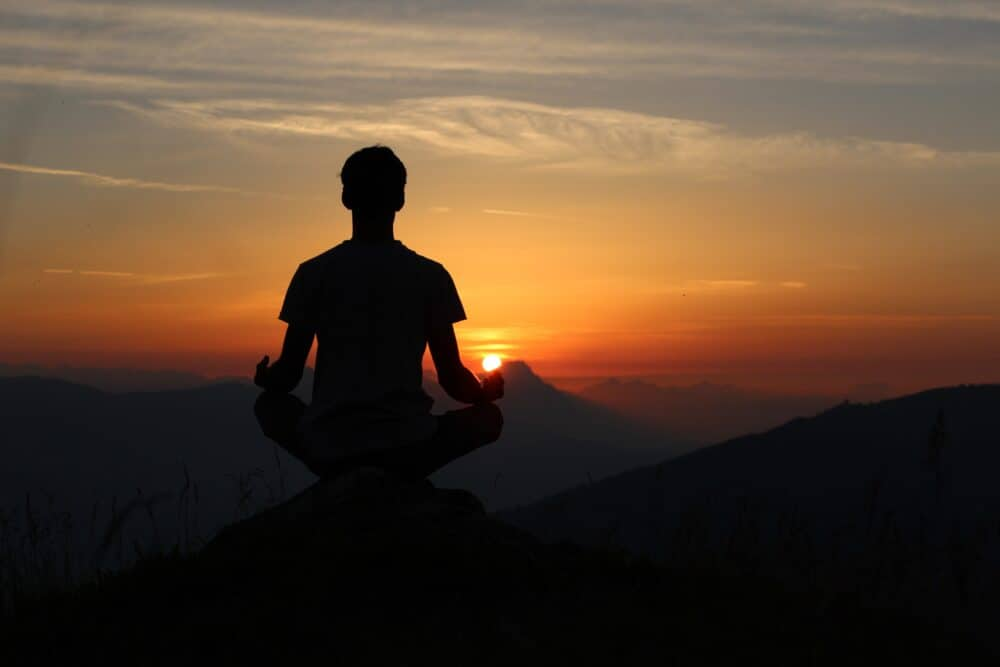 guy meditating on mountain